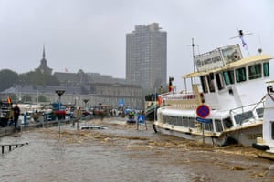 Liege, Belgium: Members of the public stand next to a damaged boat after flooding in the city.