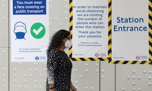 A woman wearing a face mask walks into an underground station in London