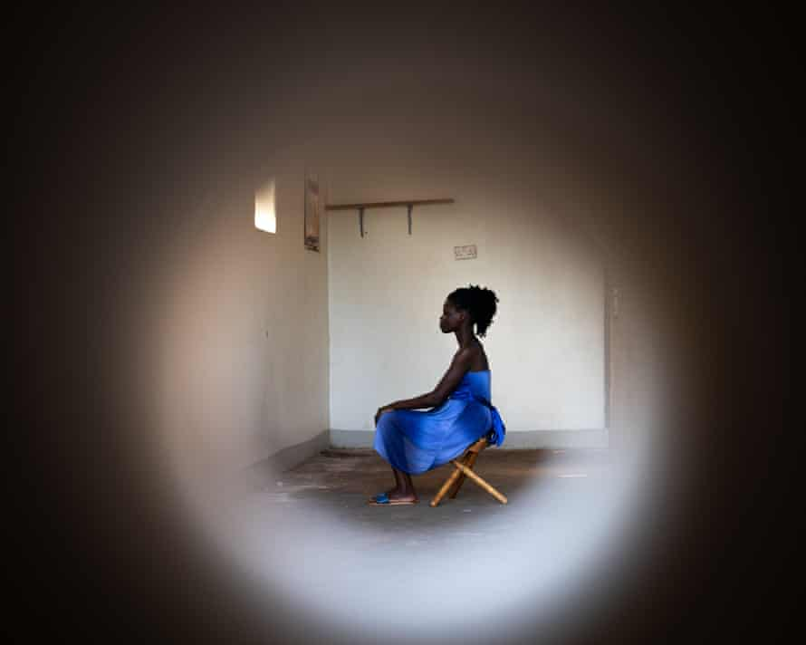Sitting in blue dress in profile looking straight ahead, seen through peephole