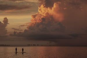 Two paddle boarders stop to watch the sunrise on a stormy morning in Sanibel, Florida, US