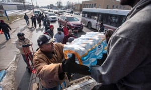 Volunteers unload gallons and cases of bottled water in front of a Flint, Michigan community center.