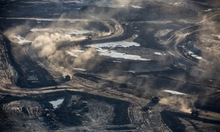 Trucks and machinery along routes within the Suncore tar sands site near to Fort McMurray in Northern Alberta.