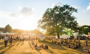 festival-goers walking against sunset at Latitude festival