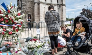 Tributes are paid at a makeshift memorial in front of the Normandy church where Jacques Hamel died.