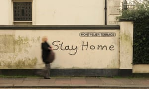 A woman passes a wall with 'stay home' painted on it
