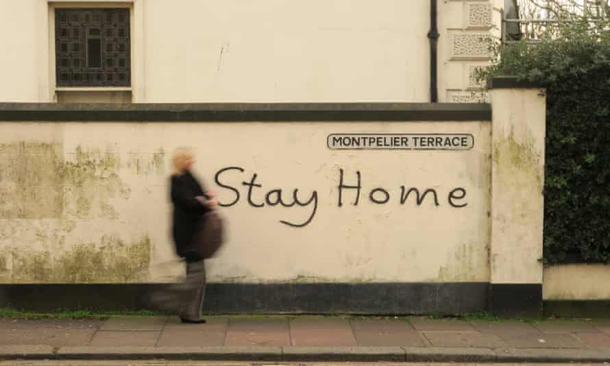 A woman in Brighton walks past a wall with 'stay home' painted on it