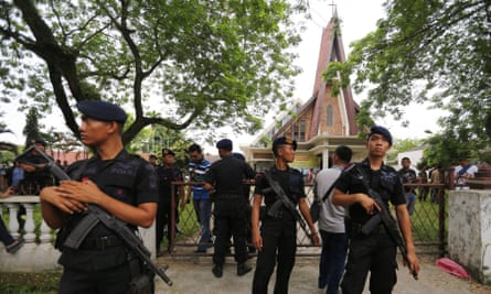 Indonesian mobile brigade policemen stand guard after an attempted suicide bombing at St. Yoseph Catholic Church in Medan.