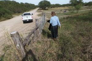 Marianna Wright walks at the center near a Border Patrol truck.
