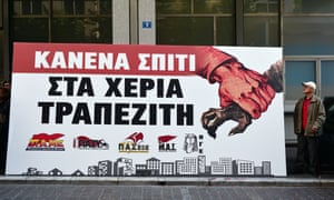 'A protester stands by a banner reading 'No house in the hands of bankers' in Athens.