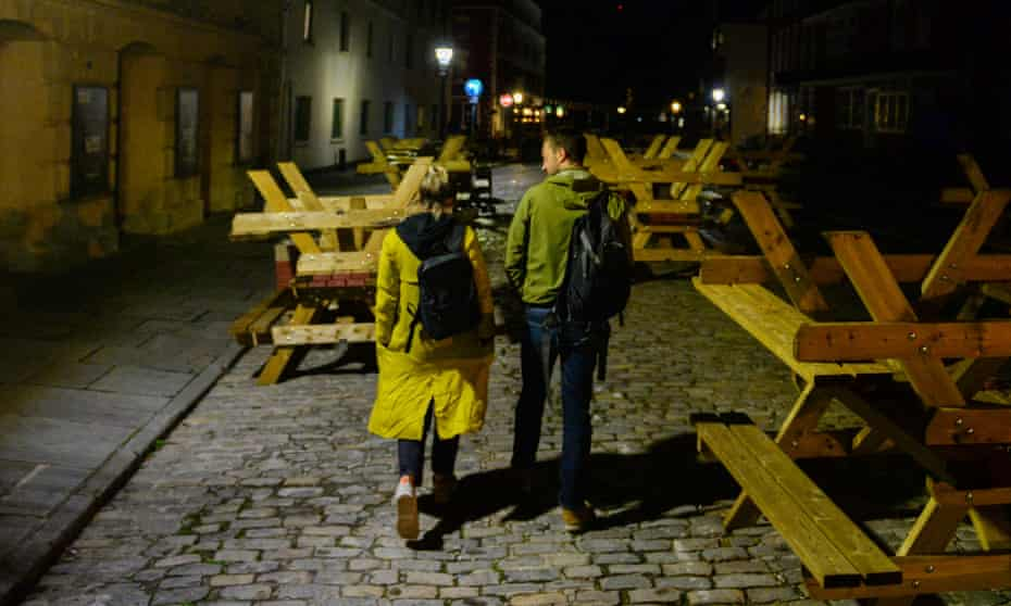 A couple walk through upturned pub seating in King Street in Bristol, England.