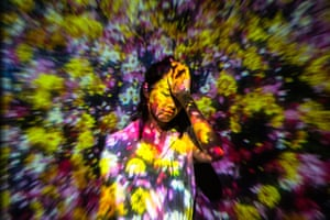 A woman disappears into a projection of flowers at the Living Digital Forest and Future Park exhibition in Beijing, China
