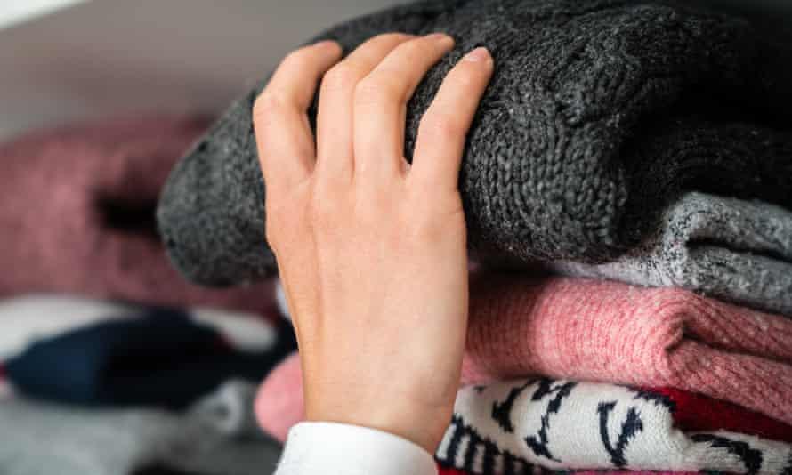 A hand reaches for a jumper on a wardrobe shelf