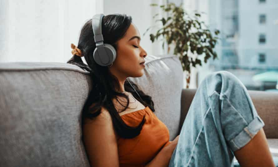 Posed by model Listening on headphones at home Shot of a young woman using headphones while relaxing on the sofa at home