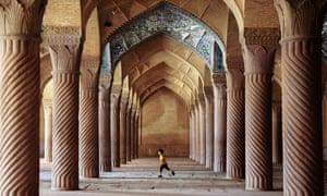 A boy runs between pillars at the Vakil mosque in Shiraz, Iran.