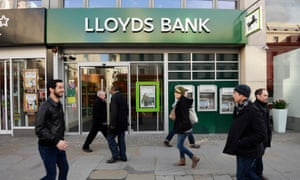 Pedestrians walk past a branch of Lloyds bank in London