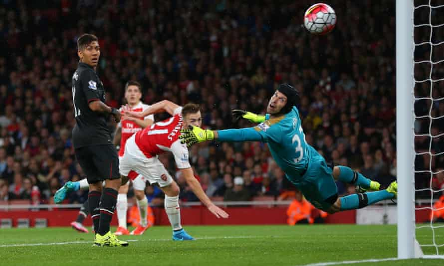 Petr Cech of Arsenal claws the ball away to deny Philippe Coutinho of Liverpool.