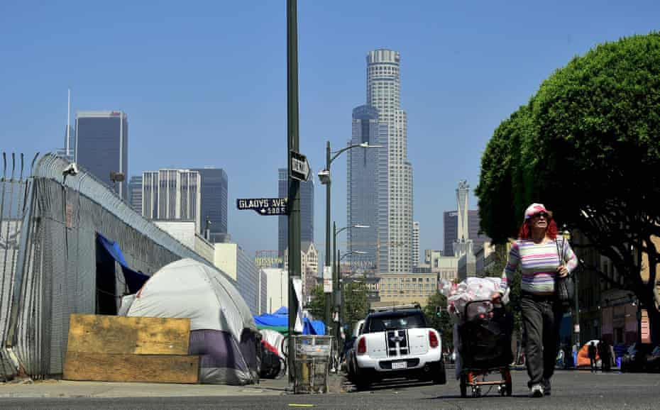 A woman pushes a cart full of her belongings past tents near Skid Row in downtown Los Angeles.