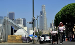 A woman pushes a cart full of belongings past tents on the sidewalk near Skid Row in downtown Los Angeles.