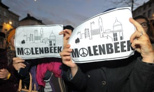 Women hold signs which say Molenbeek at a rally in the suburb to commemorate the victims of the Paris attacks