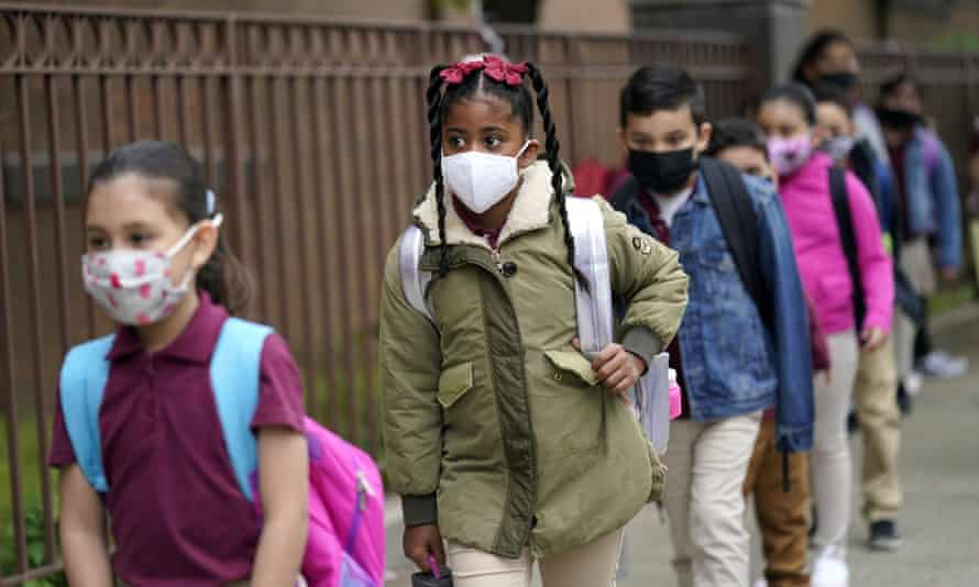 FILE - Students line up to enter Christa McAuliffe School in Jersey City, N.J., Thursday, April 29, 2021. Gov. Phil Murphy is set to announce Friday, Aug. 6 that New Jersey students from kindergarten to 12th grade and staff members will be required to wear masks in schools when the new year begins in a few weeks, as COVID-19 cases rise in the state.  (AP Photo/Seth Wenig, File)