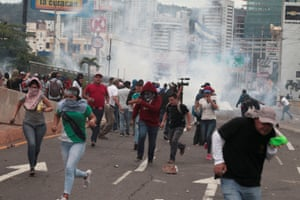 Demonstrators run away from tear gas during a protest against plans to privatise healthcare and education