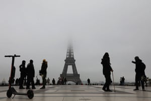 Paris, France. Tourists in Trocadero Plaza view the Eiffel Tower on a foggy morning