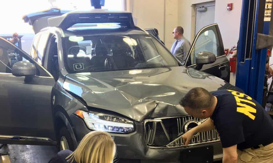 Transport safety investigators examine a self-driving Uber vehicle involved in a fatal accident in Tempe, Arizona.