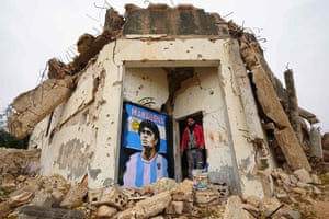 Artist Aziz Asmar stands by his painting of Diego Maradona on the wall of a destroyed home.