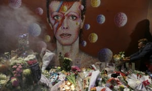 Flowers pile up near a mural showing David Bowie as Ziggy Stardust in Brixton, south London