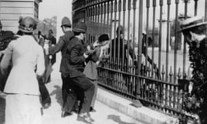 A police officer tries to remove a Suffragette from the railings outside Buckingham Palace, during a demonstration in London.