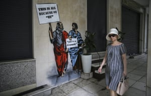 """Economy in GreeceATHENS, GREEE - JULY 18 : A woman walks past a graffiti reading """"This Is All Because of EU - You Are So Dramatic"""" in Athens, Greece on July 18, 2017, which criticizes European Union Policies of Greece. Greek government prepares to become indebted to free markets three years after debt costs started to drop. Greek economy gained trust with positive budget data incomes and releasing credit tranches after settling with the creditors. Greece plans to float 2 to 4 billion euros. (Photo by Ayhan Mehmet/Anadolu Agency/Getty Images)"""