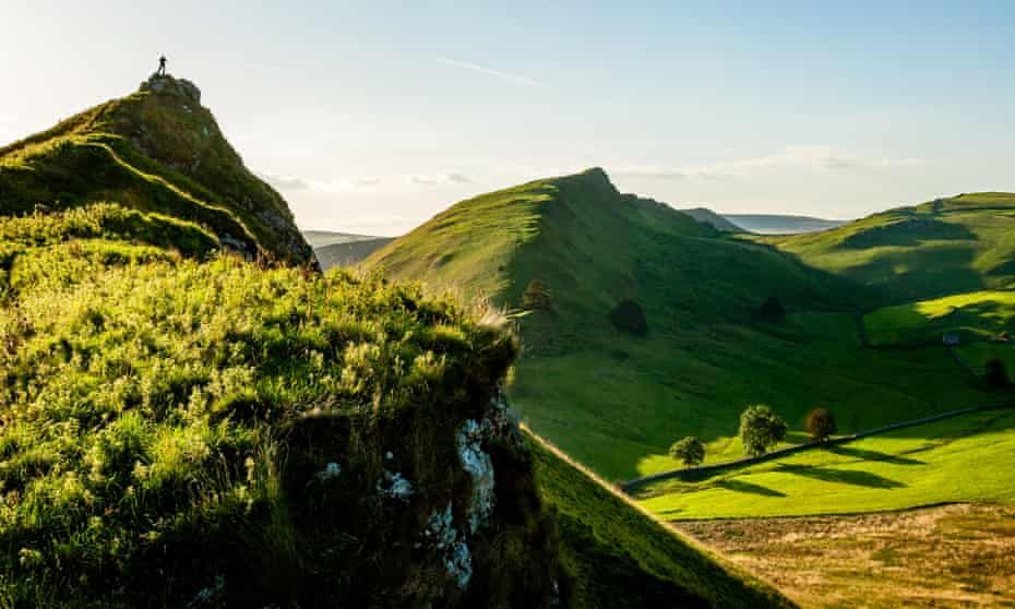 A walker on the summit of Parkhouse Hill looking across to Chrome Hill in upper Dovedale.