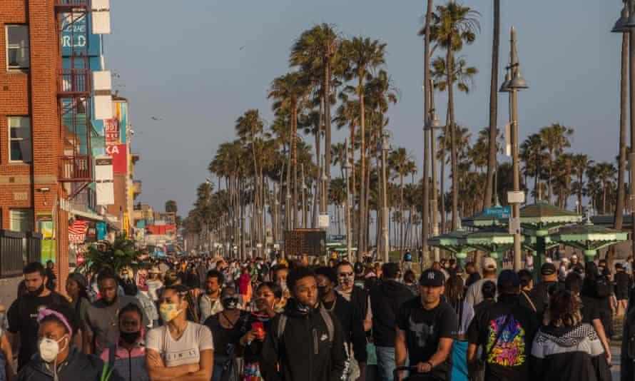 People walk at the boardwalk in Venice Beach in California on Memorial Day weekend.