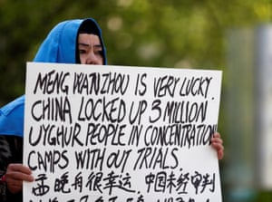 A protester holds a sign condemning China's treatment of Uighur people during a court appearance by a Huawei executive in Vancouver, Canada.