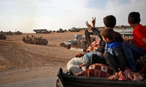 Syrian Arab civilians flash the victory sign as Turkish armoured personnel carriers and US-made M60 tanks gather in the village of Qirata on the outskirts of Manbij