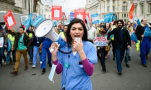 A demonstrator in scrubs uses a loudspeaker as she participates in a protest in central London. So far this year, 37% of the £6bn worth of clinical contracts put out to tender have gone to private companies.