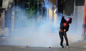 A Kashmiri protester throws teargas back at Indian police during a protest in Srinagar.