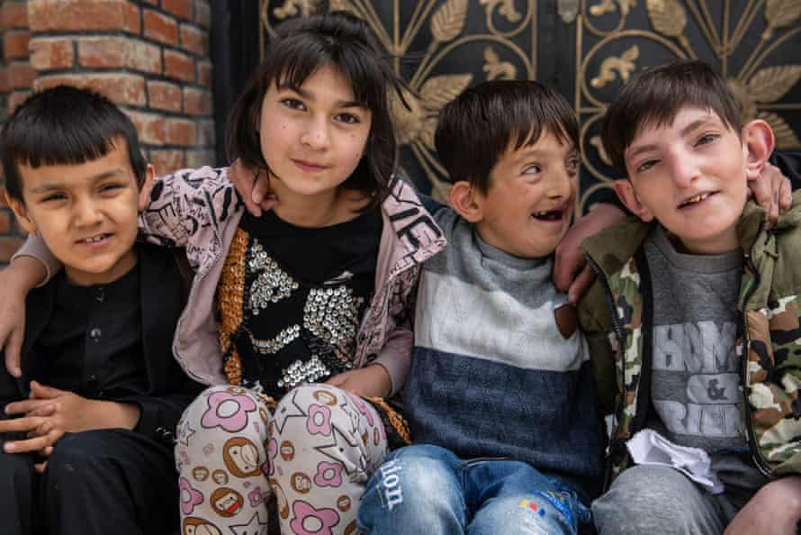 Children sit outside the Fatima Khalil school in Kabul