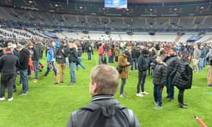 Spectators wait on the pitch of the Stade de France stadium in Paris.