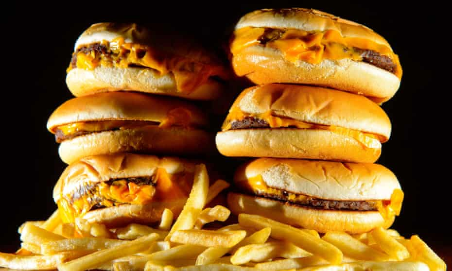 A pile of cheeseburgers and french fries.