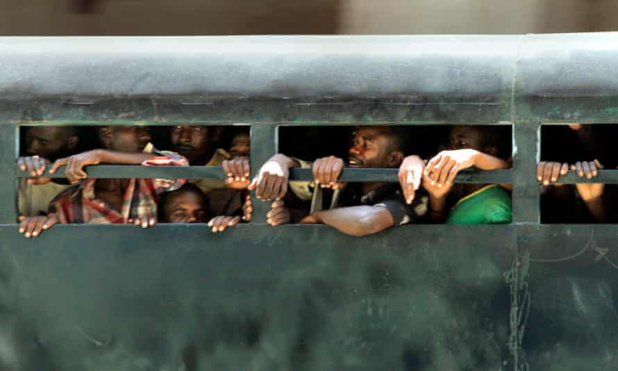 Unidentified prisoners are transported in the back of a truck through central Khartoum in Sudan.