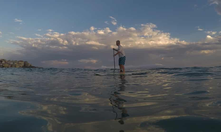 A man paddleboards at Bondi beach in Sydney during a heatwave in February.
