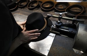 A man holds a hat inside the Borsalino hat factory, in Spinetta Marengo