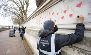 London, UK. Covid-19 Bereaved Families for Justice start their own memorial to the nearly 150,000 UK dead on a wall opposite parliament on the southern bank of the Thames near St Thomas' hospital. Bereaved and volunteers will paint hearts for each person who has died