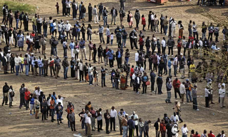 Kenyans queue to cast their votes at dusk at a polling station in downtown Nairobi, Kenya.
