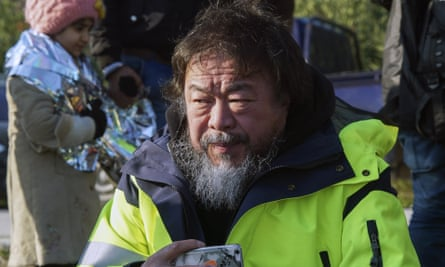 Ai Weiwei assists asylum seekers after their arrival by a dinghy from Turkey to the Greek island of Lesbos on 28 January.