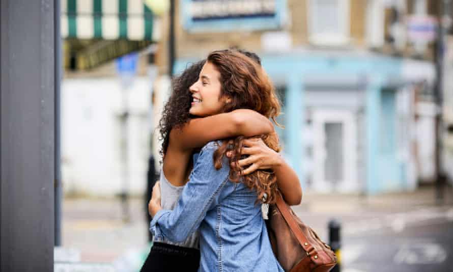 Two women hugging outside on a street.