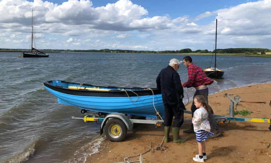 Family gets ready to launch small boat on the River Debden in Suffolk.