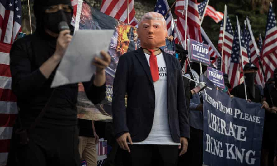 A pro-democracy protester wears a face mask of Donald Trump during a March of Gratitude rally to say thank you to the US for their support in December last year in Hong Kong, China.