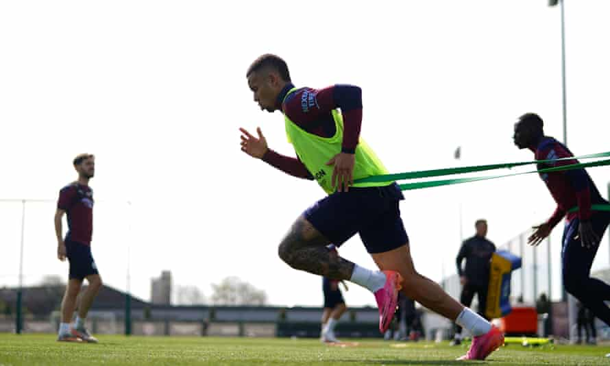 Manchester City striker Gabriel Jesus runs while wearing a resistance band during a training session.